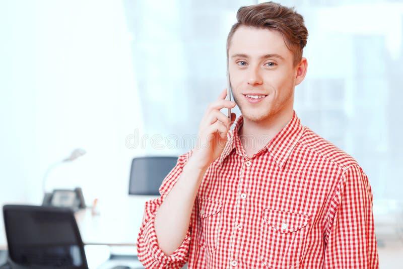 Jonge knappe bureaumanager die per mobiel spreken stock fotografie