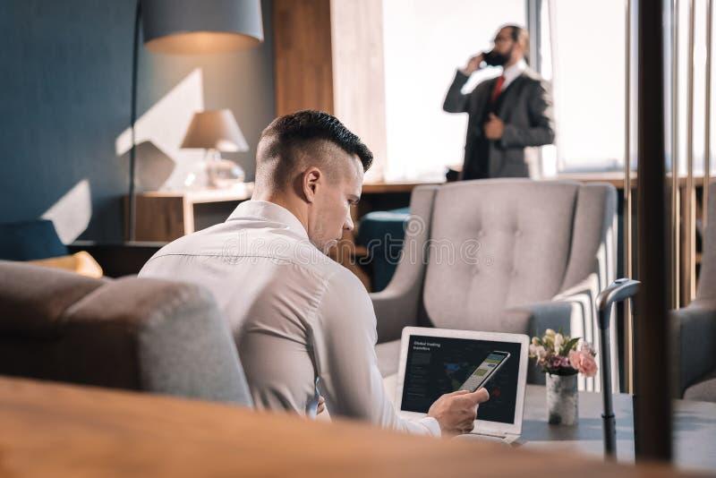 Jonge knappe ceo die aan zijn laptop in het bureau werken royalty-vrije stock foto's