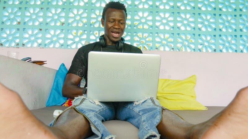 Jonge knappe en gelukkige van bedrijfs hipster zwarte afro Amerikaanse mens met laptop computer werken en hoofdtelefoons tevreden stock afbeelding