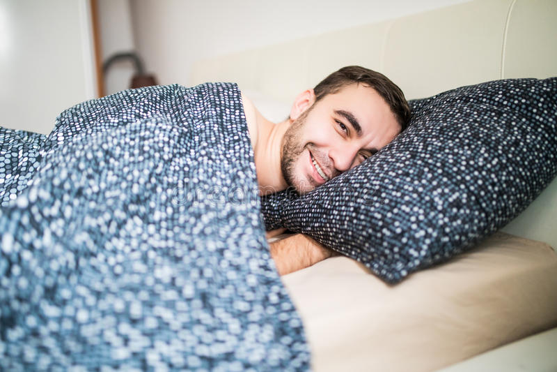 Jonge knappe gelukkige mensenontwaken op bed thuis stock foto's
