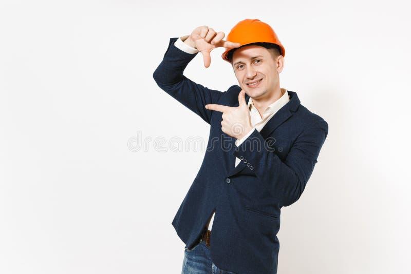 Jonge knappe glimlachende zakenman die in donker kostuum, beschermende bouw oranje helm het kadergebaar maken van de handenfoto royalty-vrije stock foto