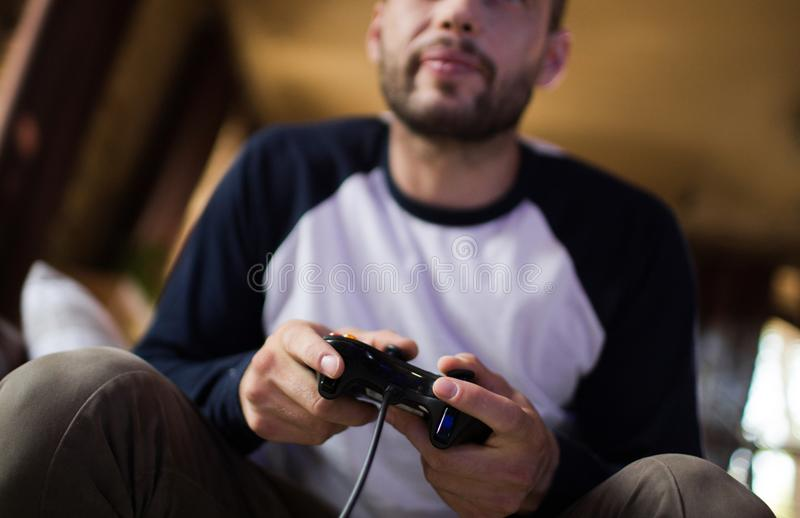 Jonge knappe het spelcontrolemechanisme van de mensenholding het spelen videospelletjes stock afbeeldingen