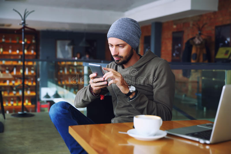 Jonge knappe hipstermens met baardzitting in koffie die mobiele telefoon, het houden van kop van koffie en het glimlachen spreken royalty-vrije stock fotografie