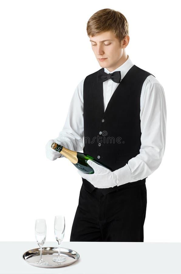 Jonge knappe kelner het openen fles champagne royalty-vrije stock foto's