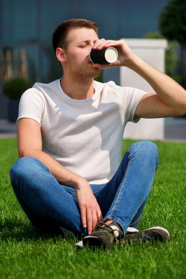 Jonge knappe kerel het drinken koffie om te gaan, mensenzitting op gras en het genieten van een van aardige zonnige dag door mode stock afbeelding
