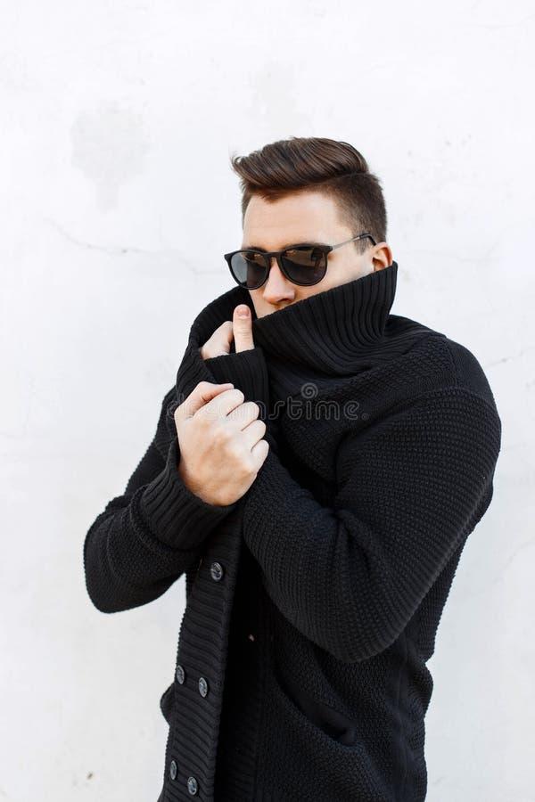 Jonge knappe kerel met haar in een zwarte sweater en zonnebril s stock foto's