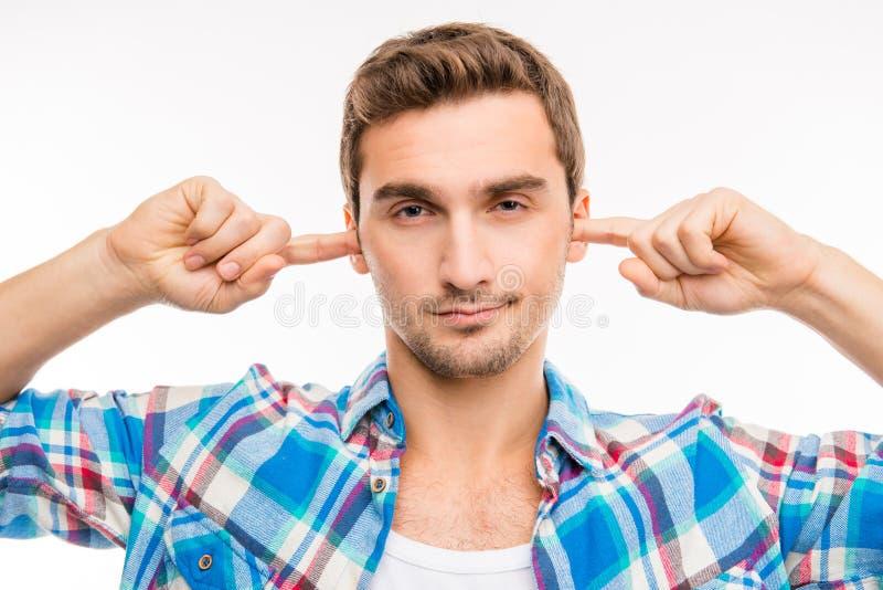 Jonge knappe man die zijn oren bedekt met het negeren van lawaai royalty-vrije stock afbeeldingen