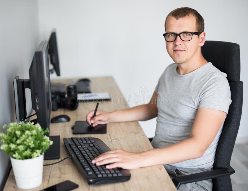 Jonge knappe mannelijke fotograaf het uitgeven beelden met computer in modern bureau of thuis royalty-vrije stock afbeeldingen