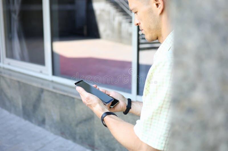 Jonge knappe mannelijke holding twee moderne smartphones in handen royalty-vrije stock fotografie