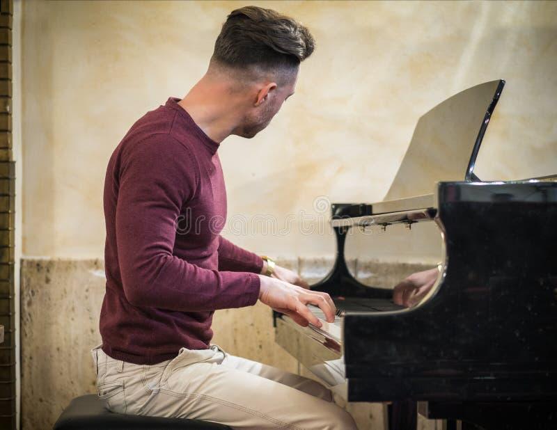 Jonge knappe mannelijke kunstenaar die klassieke piano spelen stock foto's