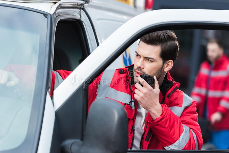 jonge knappe mannelijke paramedicus die zich dichtbij ziekenwagen en het spreken bevindt royalty-vrije stock afbeeldingen