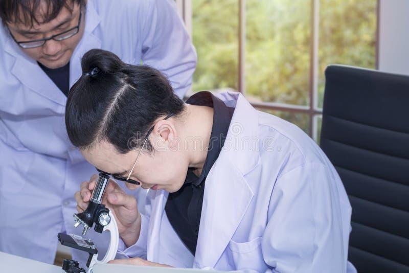 Jonge knappe medische student en onderzoekmedewerker met microscopen stock foto