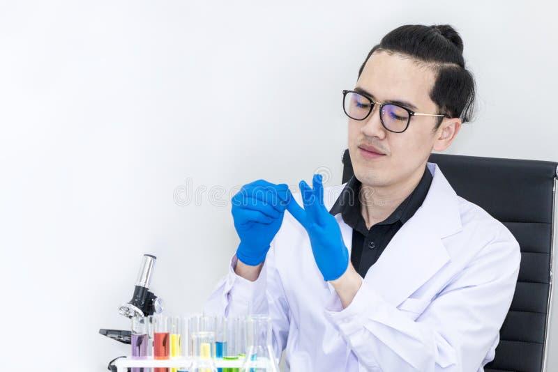 Jonge knappe medische student gezet op handschoenen dichtbij microscopen stock foto's
