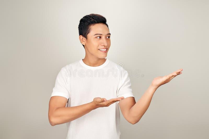 Jonge knappe mens die aan de kant met hand en open palm richten, die advertentie gelukkig en zeker glimlachen voorstellen royalty-vrije stock foto