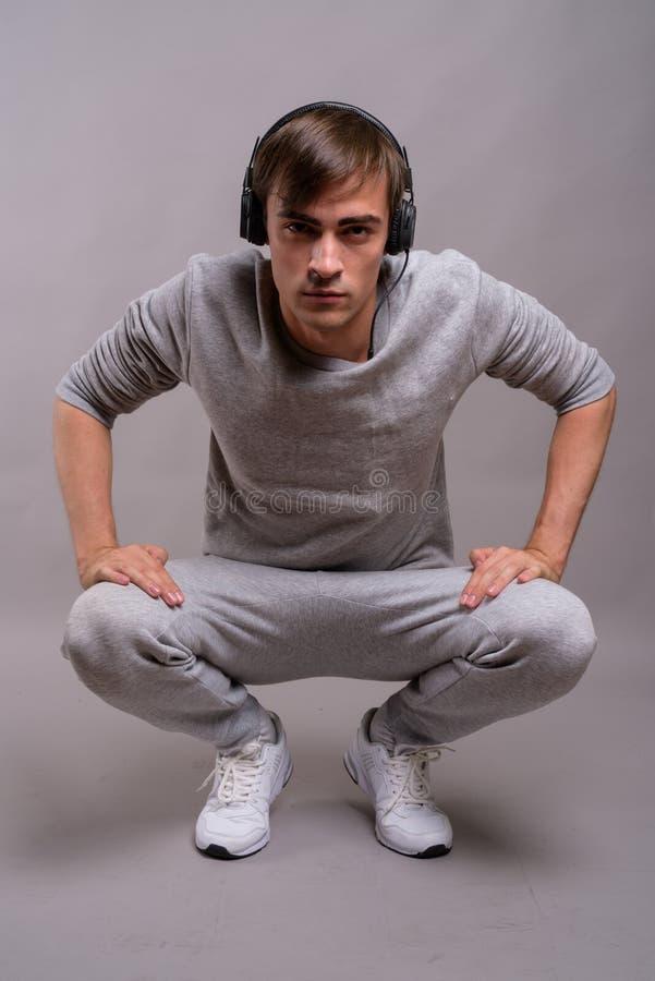 Jonge knappe mens die aan muziek luisteren en klaar voor gymnastiek tegen stock foto