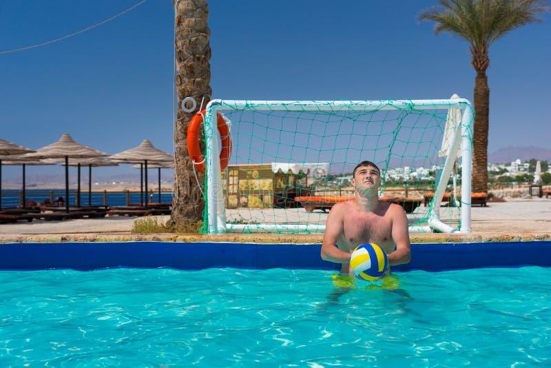 Jonge knappe mens die de bal in polo van het pool het speelwater houden royalty-vrije stock afbeelding