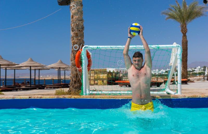 Jonge knappe mens die de bal in polo van het pool het speelwater werpen stock fotografie