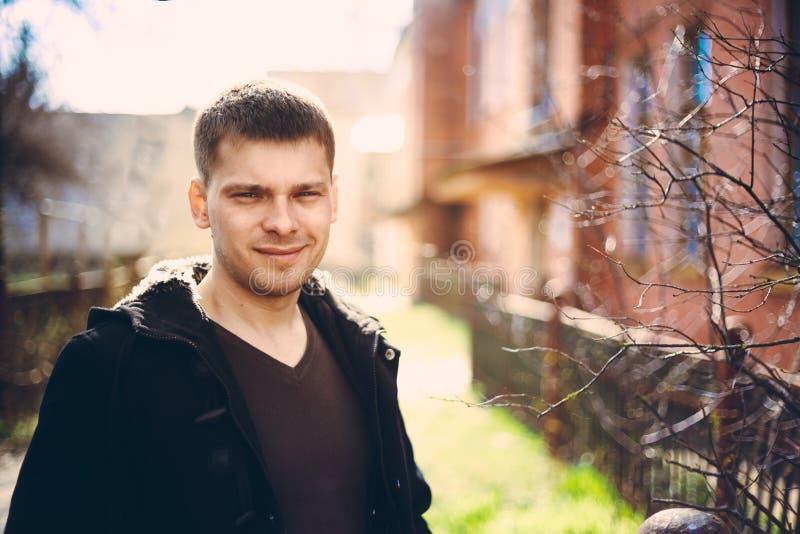 Jonge knappe mens die dichtbij oud blokhuis in de herfst of SP blijven royalty-vrije stock afbeeldingen