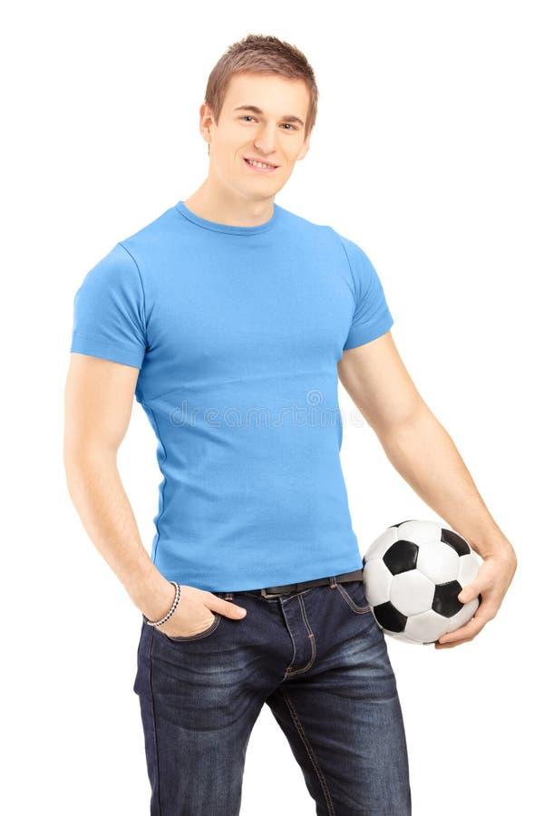 Jonge knappe mens die een voetbalbal houden stock fotografie