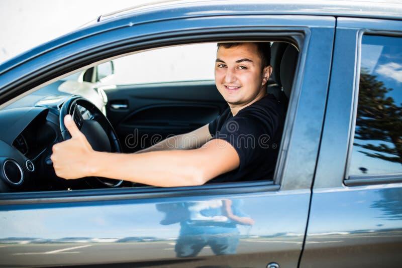Jonge knappe mens die en duimen in zijn auto glimlachen tonen royalty-vrije stock afbeeldingen