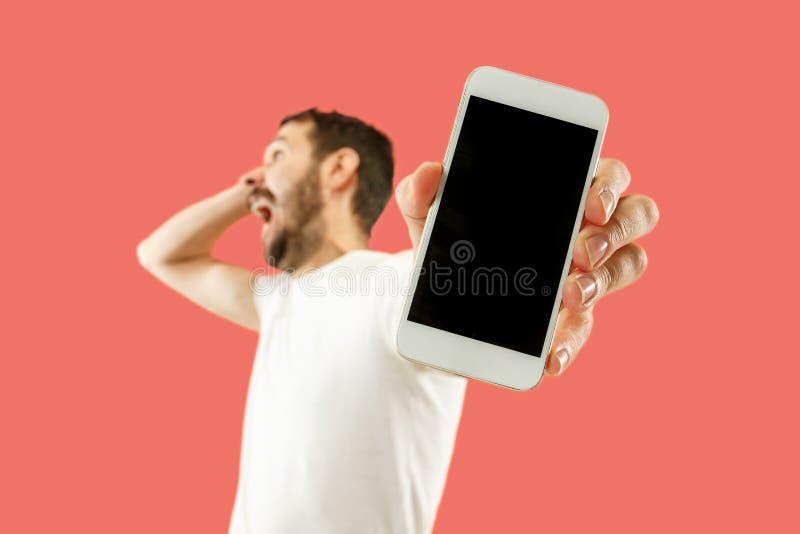 Jonge knappe mens die die het smartphonescherm tonen op koraalachtergrond wordt geïsoleerd in schok met een verrassingsgezicht stock foto
