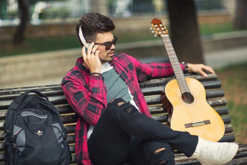 Jonge knappe mens die met hoofdtelefoons aan muziek luisteren stock afbeelding