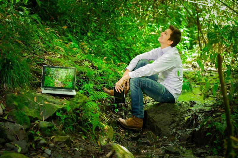 Jonge knappe mens die met laptop werken en royalty-vrije stock afbeelding
