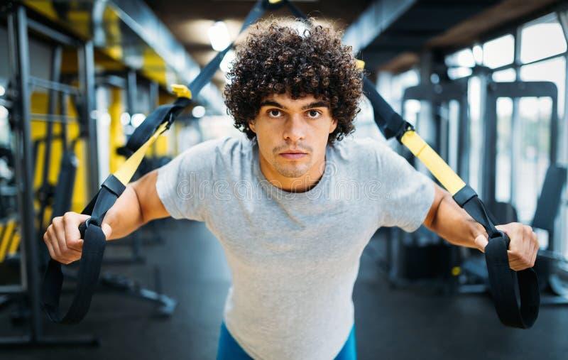 Jonge knappe mens die oefeningen in gymnastiek doen royalty-vrije stock afbeeldingen