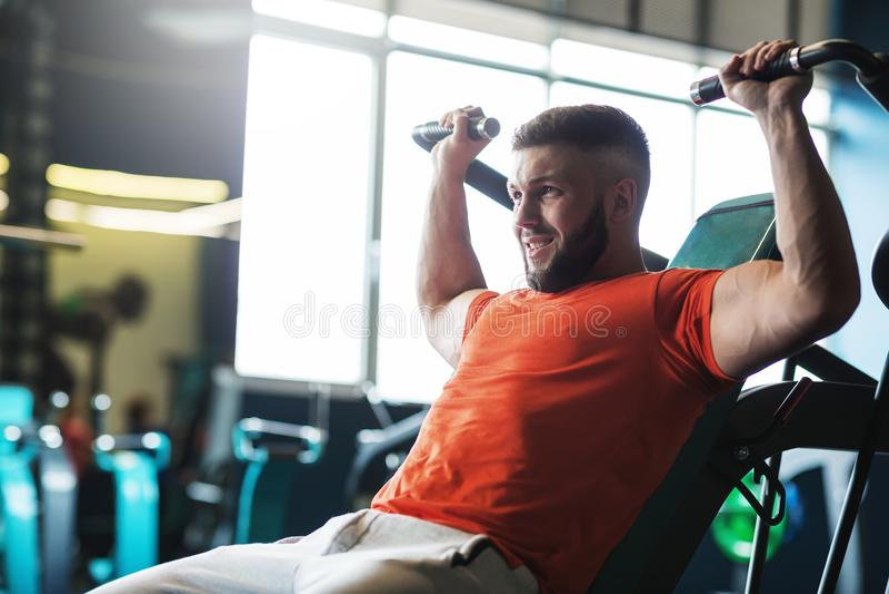 Jonge knappe mens die oefeningen in gymnastiek doen stock foto