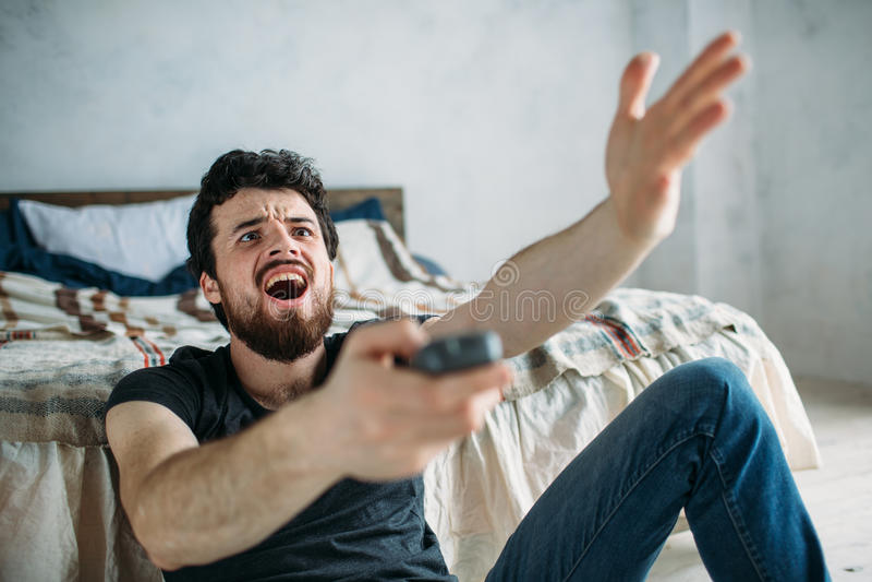 Jonge knappe mens die op TV op een vloer thuis letten royalty-vrije stock fotografie