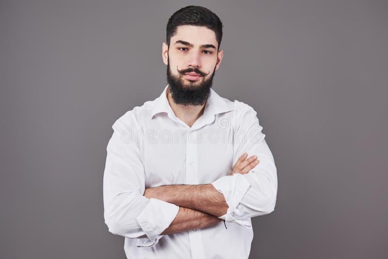 Jonge knappe mens die tegen grijze muur met gekruiste wapens leunen Een ernstige jonge mens met een baard bekijkt de camera royalty-vrije stock afbeeldingen