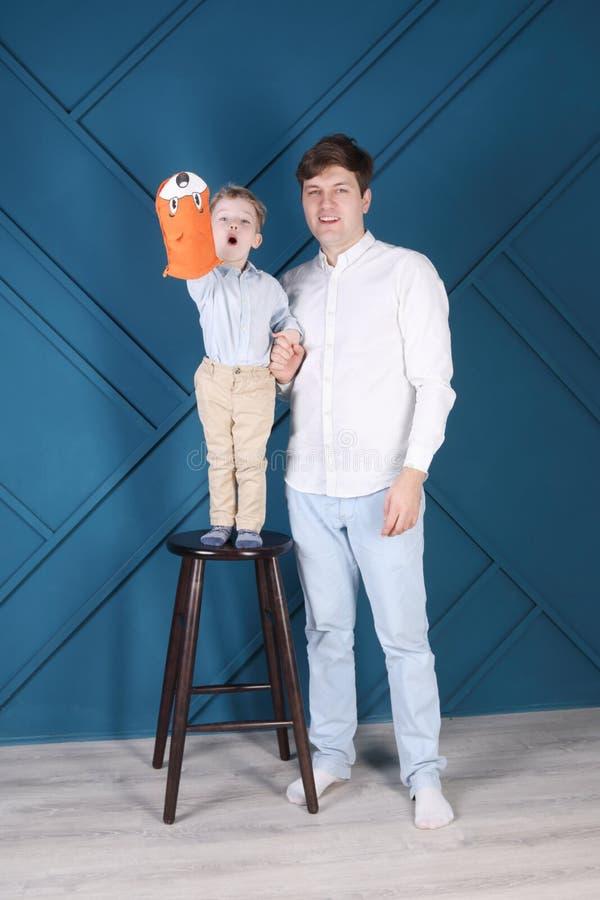 Jonge knappe mens en weinig zoon op kruk stock fotografie