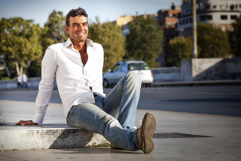 Jonge knappe mens het glimlachen zitting op de grond op stoepstraat openlucht royalty-vrije stock foto's
