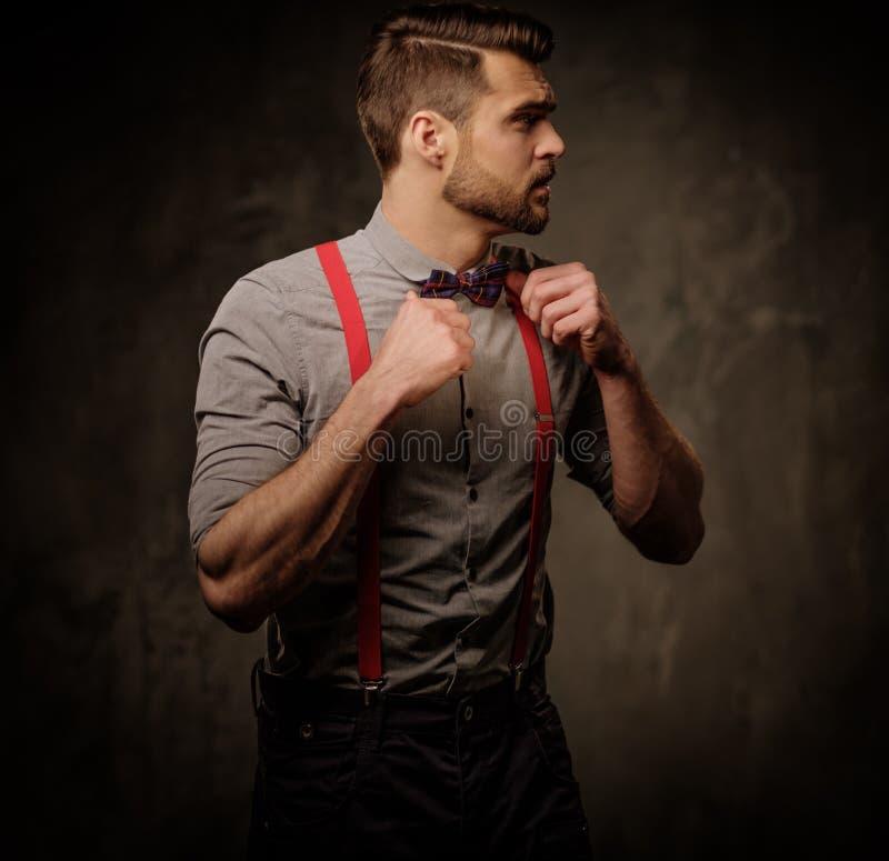 Jonge knappe mens met baard die bretels en vlinderdas dragen, die op donkere achtergrond stellen stock afbeeldingen