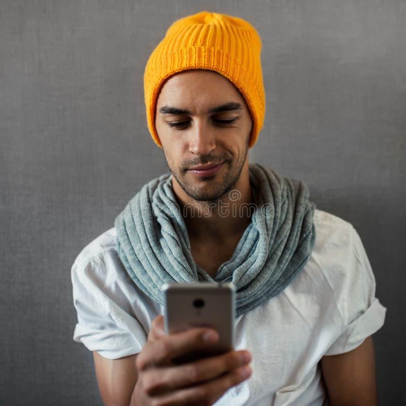 Jonge knappe mens met een apparaat, een telefoon, een lezing of het spelen Het dragen van oranje hoed en grijze sjaal op grijs stock foto