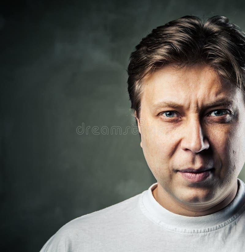 Jonge knappe mens met ernstige uitdrukking op dark royalty-vrije stock afbeelding