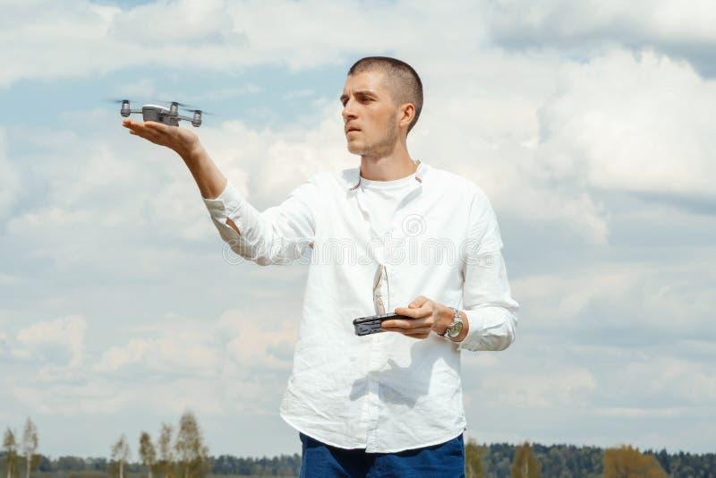 Jonge knappe mens met hommel quadcopter bij platteland bij zonnige dag stock fotografie