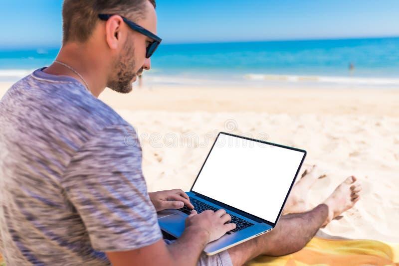 Jonge knappe mens met laptop met exemplaar ruimtespatie die op het strand onder paraplu op roeping liggen royalty-vrije stock afbeeldingen