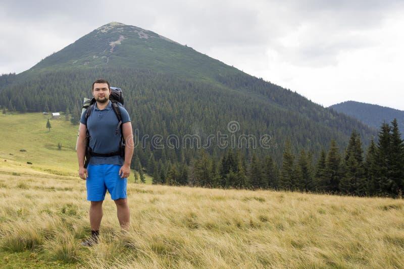 Jonge knappe mens met rugzak die zich in berg grasrijke vallei bevinden op exemplaar ruimteachtergrond van piek van de de zomer d stock afbeeldingen