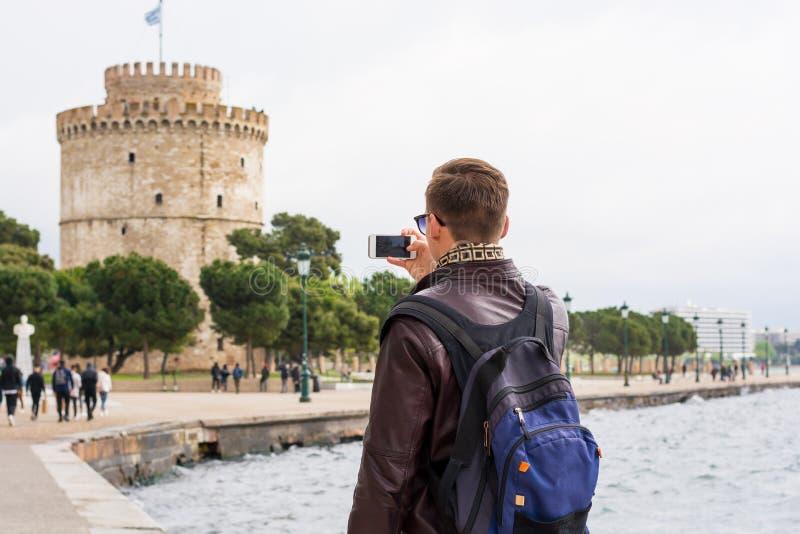 Jonge knappe mens in zonnebril, toerist, met rugzak die beelden op een smartphone nemen een Witte Toren in het centrum Thessaloni royalty-vrije stock foto