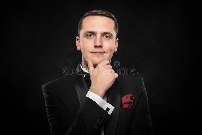 Jonge knappe mens in zwart kostuum royalty-vrije stock foto