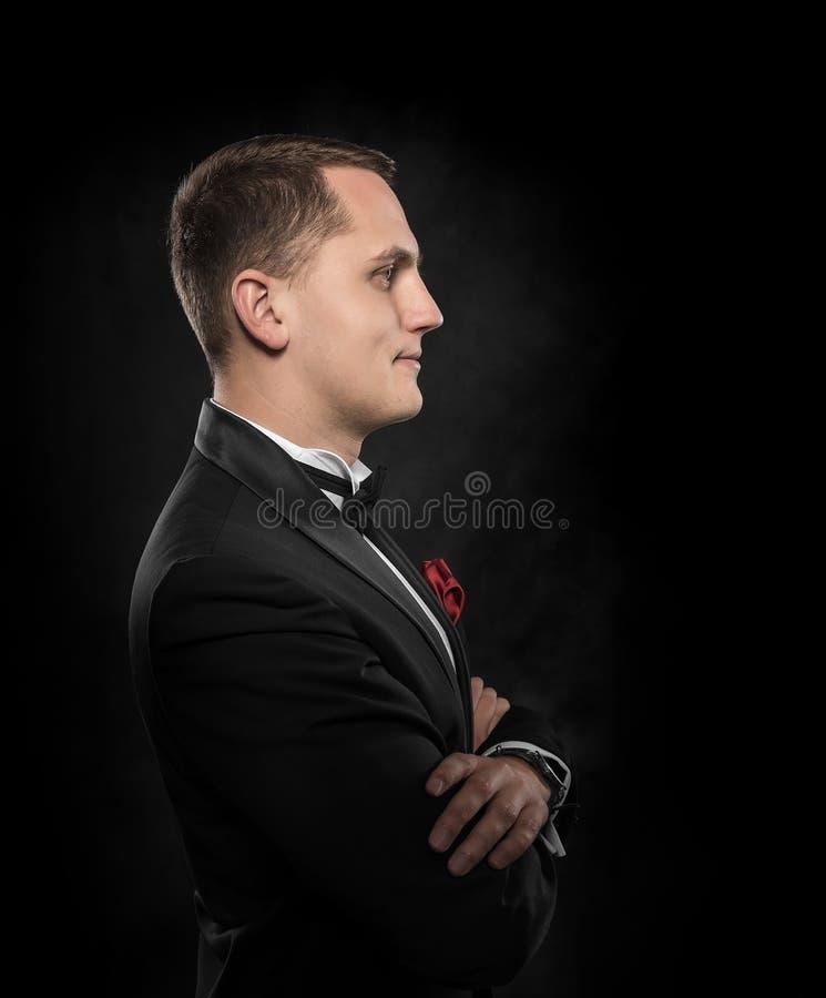 Jonge knappe mens in zwart kostuum royalty-vrije stock afbeeldingen