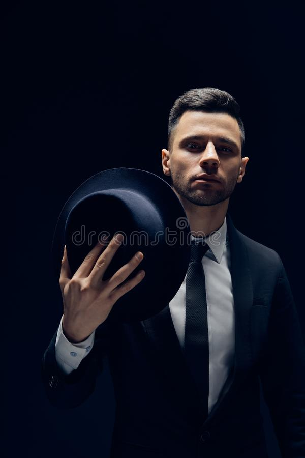 Jonge knappe mens in zwart kostuum die zijn hoed op donkere achtergrond dragen royalty-vrije stock foto's