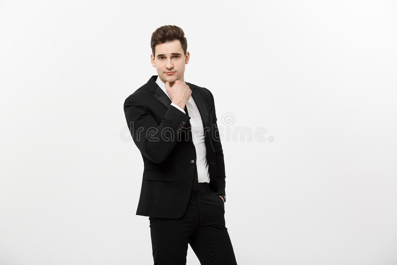 Jonge knappe mens in zwart kostuum en glazen die hetruimte glimlachen, denken of dromen bekijken geïsoleerd over wit stock afbeelding