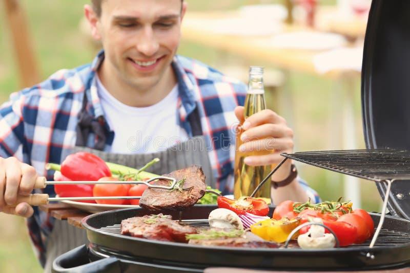 Jonge knappe mensen kokende vlees en groenten bij de barbecuegrill in openlucht stock afbeeldingen