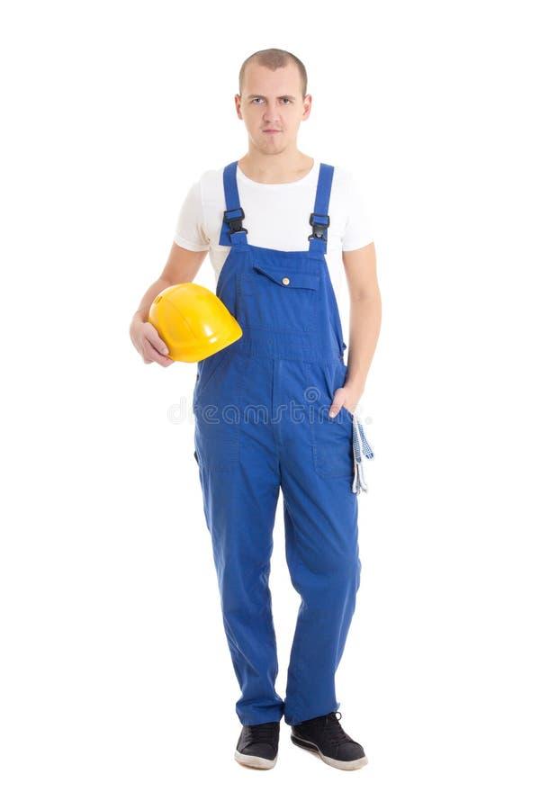 Jonge knappe mensenbouwer in blauwe eenvormige holdingshelm isolat stock afbeeldingen