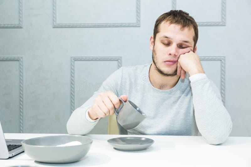 Jonge knappe mensendalingen in slaap bij ontbijt in de keuken royalty-vrije stock foto's