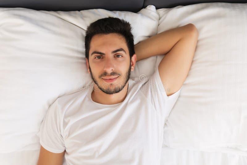 Jonge knappe mensenslaap in zijn bed stock afbeelding