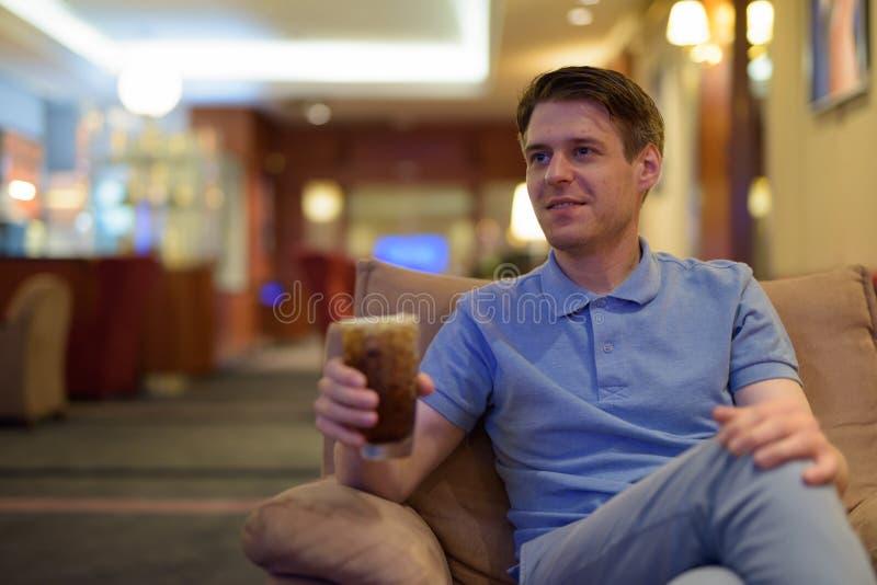 Jonge knappe mensenzitting en het ontspannen bij de hotelhal stock foto's