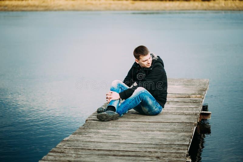 Jonge knappe mensenzitting op houten pijler, stock afbeelding